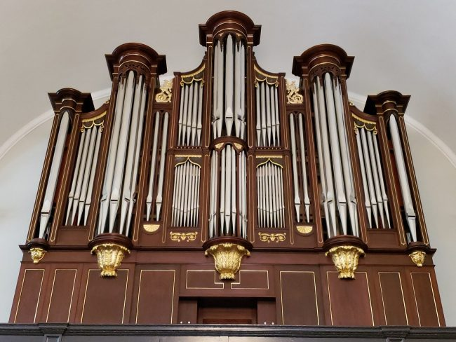 Restored pipe organ facade in mahogany with gilded carvings including five towers