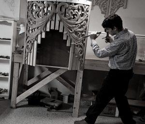Laurent Robert in his workshop carving a pipe organ tower shade in oak